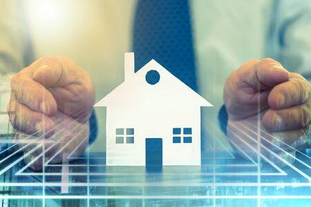 Photo pour Insurer protecting a house with his hands, color effect; multiple exposure - image libre de droit