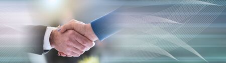 Handshake between businesswoman and businessman, light effect; panoramic bannerの写真素材