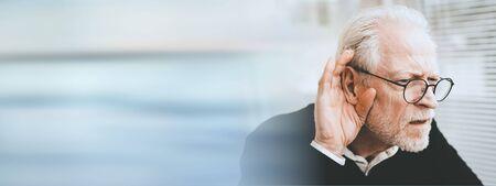 Photo pour Portrait of senior man having hearing problems; panoramic banner - image libre de droit