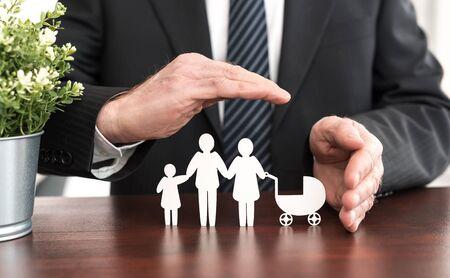 Photo pour Insurer protecting a family with his hands - image libre de droit