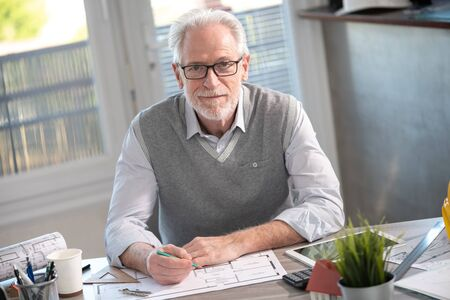 Photo pour Portrait of senior architect sitting in office and looking at the camera - image libre de droit