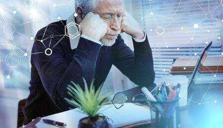 Photo pour Portrait of overworked senior businessman sitting in office; light effect - image libre de droit