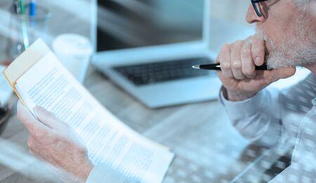 Photo pour Businessman checking a document in office; light effect - image libre de droit