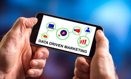 Photo pour Hand holding a smartphone with data driven marketing concept - image libre de droit