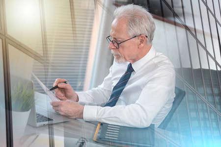 Photo pour Senior businessman checking document in office; multiple exposure - image libre de droit