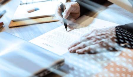 Photo pour Senior businessman reviewing terms of contract at office; light effect - image libre de droit