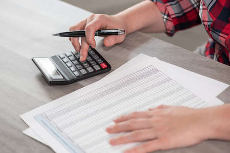 Photo pour Woman using calculator and working on financial data - image libre de droit