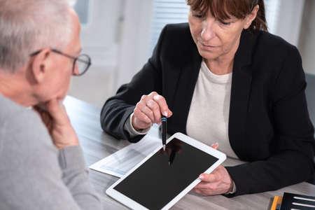 Photo pour Female financial adviser giving information on digital tablet to her client - image libre de droit