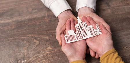 Photo pour Concept of business insurance with paper building in hands - image libre de droit