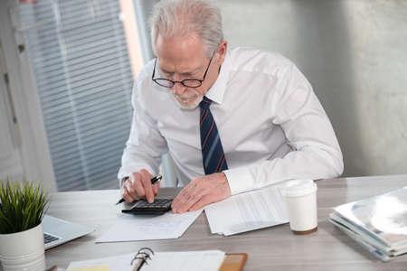 Photo pour Senior businessman using calculator. Concept of finance and economy - image libre de droit