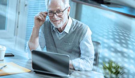 Photo pour Portrait of smiling senior businessman sitting in office; light effect - image libre de droit
