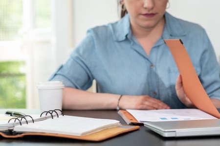 Photo pour Businesswoman opening folder with paper documents - image libre de droit