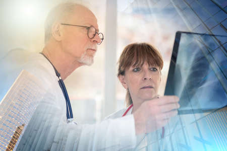 Photo pour Two doctors examining x-ray report in medical office; multiple exposure - image libre de droit