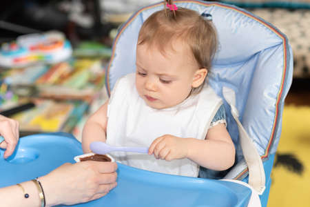 Photo pour Cute baby girl eating tasty food and learning using spoon - image libre de droit