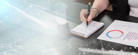 Photo pour Businesswoman analyzing marketing data and taking notes; panoramic banner - image libre de droit