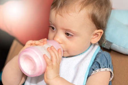 Photo pour Cute baby girl drinking milk from bottle - image libre de droit
