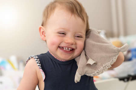 Photo pour Happy baby girl holding her cuddly toy against her - image libre de droit