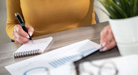 Photo pour Businesswoman analyzing marketing data and taking notes - image libre de droit