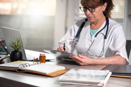 Photo pour Female doctor taking notes on clipboard at workplace - image libre de droit