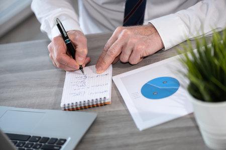 Photo pour Businessman analyzing marketing data and taking notes - image libre de droit