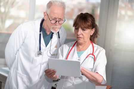 Photo pour Two mature doctors discussing about medical report on digital tablet - image libre de droit