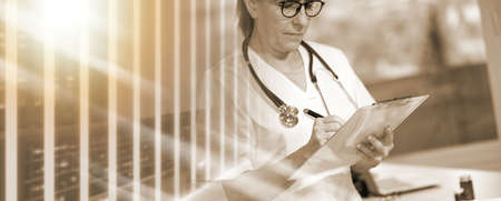 Photo pour Female doctor taking notes on clipboard in medical office; multiple exposure - image libre de droit