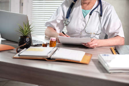 Photo pour Female doctor reading medical report in medical office - image libre de droit