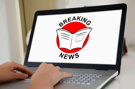 Photo pour Hands on a laptop with screen showing breaking news concept - image libre de droit
