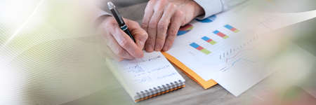Photo pour Businessman working on financial results and taking notes on notepad; panoramic banner - image libre de droit