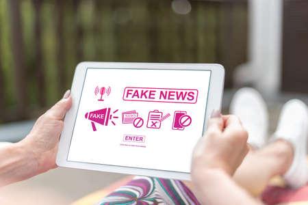Photo pour Female hands holding a tablet with fake news concept - image libre de droit