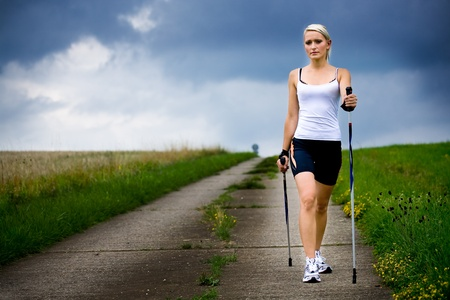 a young woman making nordic walking. outdoor shoot.