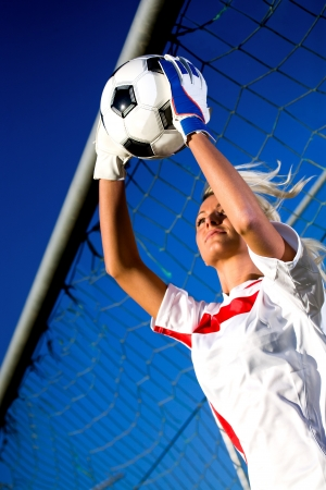 goalkeepers hands holding a soccer ball
