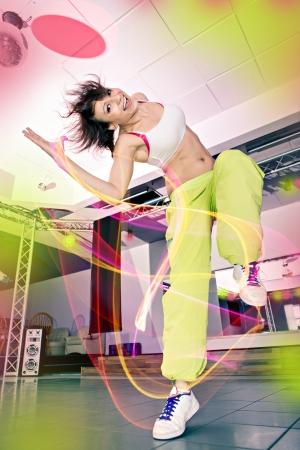 Foto de young woman in sport dress at an aerobic and zumba exercise - Imagen libre de derechos