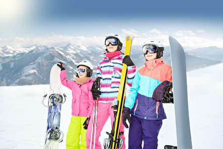 two teenage girl and a woman skiing alpin in the mountains