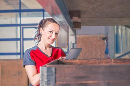 Photo pour A young female warehouse worker in a manufacturing plant - image libre de droit