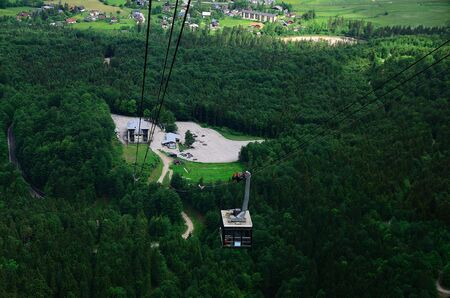 high cable car on a mountain with forest