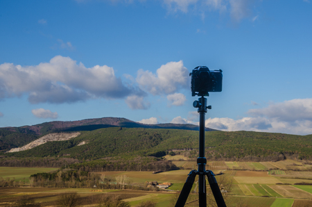 camera with tripod and green landscape