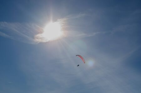 paragliders floating at the sky with sun rays