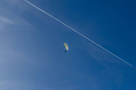 paragliders with airplane at blue sky