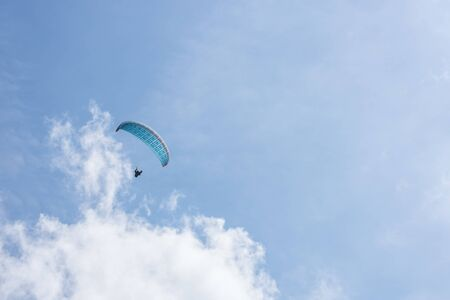 Floating blue paraglider in the sky in summer