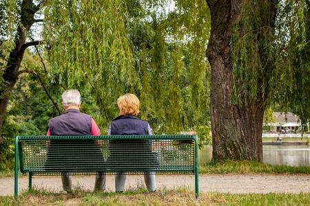 Photo pour Senior couple on a bench in a park at a lake, shot from behind - image libre de droit