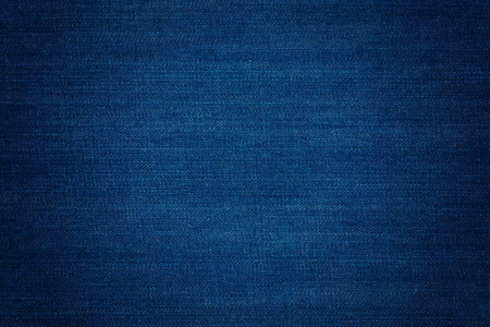 Dark blue denim background, detailed texture with vignette