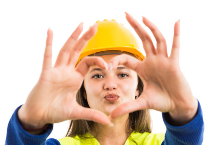 Foto per Young pretty woman architect or engineer showing heart sign and kiss lips gesture as cheerful constructor concept isolated on white background - Immagine Royalty Free