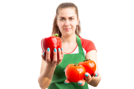 Young female supermarket or hypermarket employee holding red pepper and tomatoes as fresh vegetables promotion concept isolated on white background