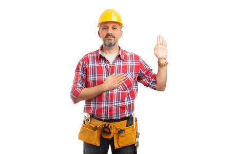 Serious builder swearing with one palm up and other hand on heart isolated on white studio background