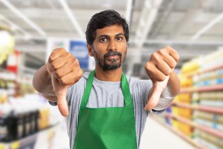 Photo pour Indian supermarket or hypermarket employee man making double thumbs-down gesture as dislike concept - image libre de droit