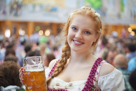 Foto de Portrait of cheerful young woman wearing traditional dirndl and holding the 1 liter beer stein at Oktoberfest - Imagen libre de derechos