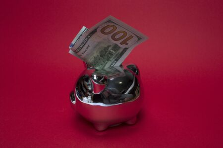 Photo pour Mirrored silver piggy bank with one hundred dollar bill on red background. The concept of banking services loans and deposits, finance, savings. Layout for design, copy space. Economy and budget. - image libre de droit