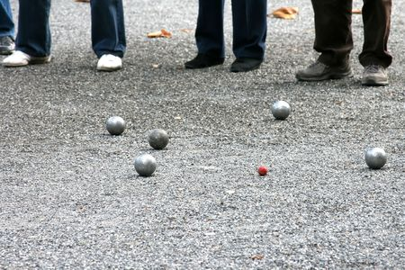 Traditional game with metal balls in France- jeu de boules (petanque) – selective focus.