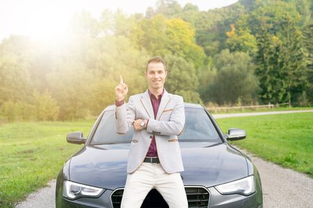 Young, happy, business man in the car. Man in a suits standing by the expensive, sport car. Successful young man.